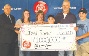 WV Lottery Director John Musgrave with one million dollar winner David Feamster and his wife Tammy of Rupert at the WV Lottery headquarters in Charleston Monday. Also pictured are Feamster's daughter Samantha and sons Noah and Logan.
