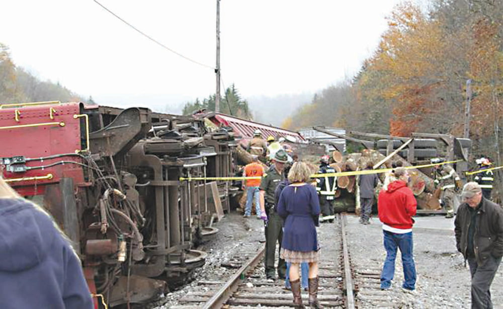 Scene at Cheat Mountain shows large heavy logs jumbled beside two toppled train cars