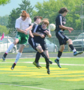 Cordel Bostic, in white, jumps high to head in the second goal in a 3-1 victory by Greenbrier East High School over Point Pleasant. The game was played Saturday, Sept. 20, in Lewisburg. (Photo by Mark Robinson)