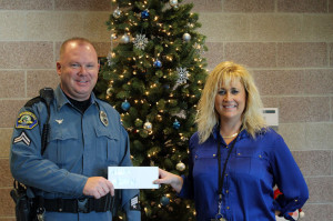 "On Dec. 18, Lewisburg Elementary School's Student Council held a ""Jingle Bell Ball"" for 3rd-5th grades to raise money for the Fraternal Order of Police's ""Shop with a Cop"" program. Pictured: Corporal John McClintic, Fraternal Order of Police receiving $500 from Terri Hall, LES Student Council Advisor."