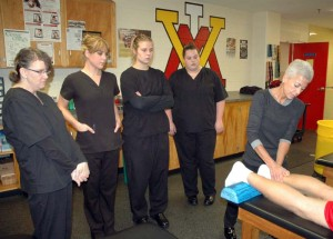 "Gloria Lawrence (far right), head of the Massage Therapy program at Dabney S. Lancaster Community College, demonstrates proper techniques to several of the students in her fall course during a clinical session in the Department of Sports Medicine at the Virginia Military Institute in Lexington. ""At VMI, cadets are treated in accordance with Orthopedic massage protocol to address deactivation of trigger points, reduction of adaptive load (biochemical, biomechanical) and/or enhancement of lymphatic and venous drainage to restore range of motion and enhance athletic performance,"" says Lawrence. ""During the Spring 2015 semester, students will be continuing with clinical rotations at the Duke Cancer Center in Fishersville."" Lawrence, who recently earned a national certification as a Natural Health Practitioner, has designed and developed the two-semester program to provide each student with experiential off-campus clinics for the most expansive skill-set training. ""This program is uniquely different from all other programs offered in Virginia,"" notes Lawrence. ""The U.S. Bureau of Labor Statistics continues to project a 20-23 percent demand. At DSLCC we are committed to changing lives by changing futures, one student at a time."" Students looking on are, from left: Doris Balser of Clifton Forge, AdriAnne Reyns of Covington, Cheyenne Adams of Buena Vista and Christa Thomas of Covington.  Clinicals for the College's program include hours at a wide variety of settings, such as retirement centers, hospitals, and sports-related venues, only a few of the many options for employment after completion of the program. For information regarding Fall 2015 enrollment, please contact Lawrence at 540-461-3447."