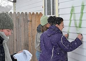 Pretty Penny Café owner Blair Campbell joins community members and friends Joanna Burt-Kinderman, left, and Amy Cimarolli, in removing the racial slur that was spray painted on the restaurant last Wednesday. With a little elbow grease, determination and brake fluid, the words were removed. (S. Stewart photo)