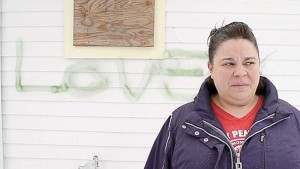 Pretty Penny Café owner Blair Campell stands in front of the green lettering that was spray painted on the side of her building. The hateful, racial slur prompted Campbell and her friends to go in a positive direction - engaging the community in a new conversation. (S. Stewart photo)