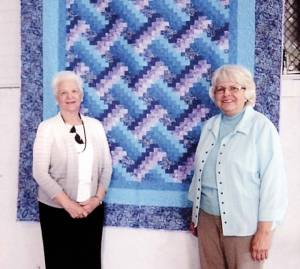 Marjorie Witcher, member of the Alderson Community Center Board (left) and Lucinda Ward, president of the Alderson Quilt and Craft Club with one of the beautiful quilts that were shown at the Alderson Quilt Club's successful Quilt Retreat which was held on Apr. 30 through May 2 of this year.