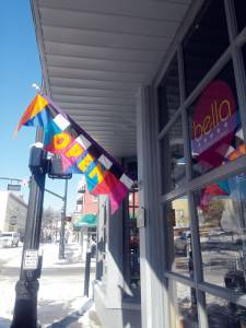 """An """"Open"""" sign hangs in front of Bella, the Corner Gourmet, a downtown Lewisburg shop that is celebrating five years in business this month. The Lewisburg Shopping District draws tourists from all over the region and is a large driver of local tourism.  (Photo courtesy of Tamera Pence)"""