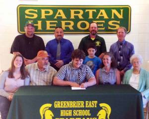 Greenbrier East High School Senior Evan Roberts (seated center) signs to wrestle at Wheeling Jesuit University. In attendance at the signing were: Standing: Coaches Joe Heath (left), Lou Withrow, Mark Solak and Brian Miluk; Seated: sister, Haley Roberts (left); father, Patrick Roberts; brother, Calvin Roberts; mother, Patricia Roberts and grandmother Stella Lewis.