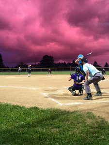 The Greenbrier Girls Softball League's 13-and-under playoffs took place under a phenomenal sunset Tuesday evening, as the sky changed from pink, to violet, to a deep blue. Here, batter Tucker Nunley, daughter of Cheryl Nunley, of Lewisburg's Wyld Thangs, faces off against Monroe County's Lady Vipers on the Greenbrier East baseball field. Wyld Thangs won 16-4. (Photo courtesy of Jenny McClung)