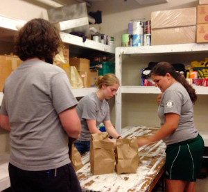 Abby, Josiah and Kendra prepare healthy snack packs for kids to take home for the weekend.