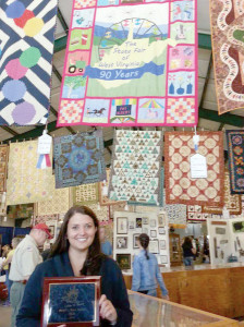 """Gloria Tuckwiller with her quilt called """"Family Traditions,"""" which won the People's Choice Award at last year's State Fair Quilt Show. Tuckwiller designed and made the quilt to commemorate the fair's 90th anniversary. The quilt depicts the shape of the state of West Virginia in the center surrounded by mountains, a Ferris wheel, and fireworks in the background and a 90-year banner in the foreground. This centerpiece was then framed by 18 individually designed squares, each one depicting a different aspect of the fair. Some of the designs, which were made using the paper piecing applique quilting technique, included a race horse, cow, flowers, and tractor. Tuckwiller, 29, has made 10 quilts since she began quilting approximately 10 years ago, including another originally designed quilt depicting the Fat Albert carnival game at the fair that she exhibited a few years ago. Tuckwiller plans to enter the State Fair Quilt Show again this year."""