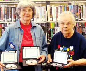 Jeanne Brenneman (left) presents art videos to Assistant Librarian Novella Perkins of the Rupert Public Library in memory of Betty McClung, Eddie Keeney and Aleta McCaffrey