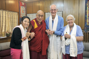 Hanno Kirk and Jo Weisbrod, both holding small golden Buddhas, a gift from the Dalai Lama, at the conclusion of their visit with His Holiness, together with trip organizer Minh Chau Le (right).