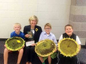"""Top winners of Annual Sunflower Contest at Lewisburg Elementary: In a field of 43 participants, Gavin Pyne (left) was the winner in Mrs. Stover's 4th Grade Class with his 52"""" sunflower entry; Townley Hamilton, Conservation Chair and President of Lewisburg House and Garden Club congratulated the top winners, Lawson Hamilton displays his winning entry of 57"""" for the 5th Grade in Ms. White's Class and the overall winner of the School's Sunflower Contest, and John Wade was runner-up with his 53"""" sunflower entry from Mrs. Sheppard's 3d Grade Room.  President Hamilton also presented Lawson a book on the """"Birds of West Virginia"""" and a check for $25 as an award for his achievement.  All students received certificates from the Club who participated in the Contest."""