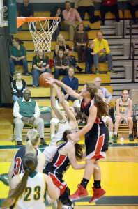 Greenbrier East's Lauren Lindsay falls backward with a rebound, as St. Albans guard Zoei Kirk reaches for the ball, in a game played Saturday evening, Dec. 12, at the Spartans' gym. Greenbrier East won the game, 60-54. Photo by Mark Robinson