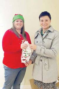 Sarah Elkins, director of marketing at Greenbrier Technologies (right), delivers Christmas dinner and gift bags to Brittany Nutter, victim advocate with the Family Refuge Center, for their Annual Kid's Party.