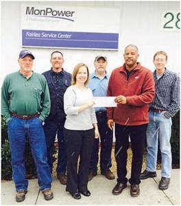 Front Row: Kasey Carter (left), director of Communities In Schools of Greenbrier County, receiving the donation from Darrewll Hughes of Mon Power; Back Row: Mon Power employees Calvin Boothe (left), Jesse Martin, Randy Redden and Clint Dixon.