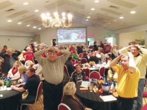"A packed house plays ""Heads & Tails"" while the NCAA tournament plays at March Rotary Madness in 2014"