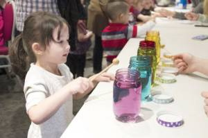 Kids were encouraged to play a song on jars filled with varying amounts of water, similar to a xylophone. Volunteers explained that different amounts of water produced different sounds because of changes in how sound travels through the water. (Photo courtesy of Pat Bauserman, WVSOM)