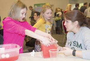 """Kids dipped their hands into simulated blood to learn about the functions of different blood cells. Red water beads represented red blood cells, which carry oxygen through the body. Ping pong balls represented white blood cells, which are the """"superheroes"""" of the blood that eat and digest germs. Foam squares represented platelets, which clump together to form clots when a person gets cut. (Photo courtesy of Pat Bauserman, WVSOM)"""