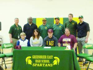 Greenbrier East High School senior Jonathan Carr has signed with the University of Charleston to play  baseball next year. Pictured at the signing are: Front Row: Logan Carr (left), Kristi Carr, Jonathan Carr and Gene Ray Carr; Back Row: Ben Routson, Athletic Director (left), Head Football Coach Ray Lee, Head Baseball Coach Cory Mann, Assistant Baseball Coach Scot Brown, Assistant Football Coach Jared Sams and Travis McClintic, physical therapist. (Photo by Mark Robinson)