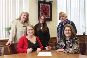 Greenbrier Valley Theatre Education Director Courtney Susman, (seated left) and Dr. Kendra Boggess, Concord University President (seated right) sign the agreement. Back Row: Concord University Instructor of Communication Arts Karen Vuranch (left); Kilie Mullins, a student at Concord; and Greenbrier Valley Theatre Producing Artistic Director Cathey Sawyer.