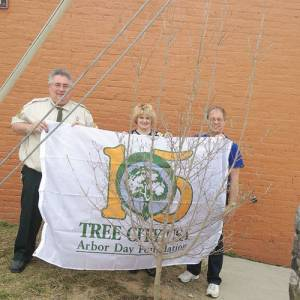 Andy Sheetz, WV Division of Forestry specialist, Reba Mohler, City Administration and Doug Hylton, president Ronceverte Tree Board hold the presented flag from the Division of Forestry and the tree planted in celebration of Arbor Day.
