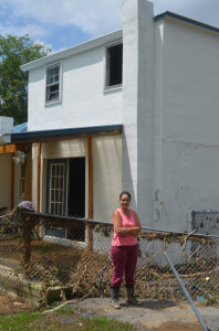 Kimberly Green stands beside the back porch of her house. She and a friend climbed out an upstairs window onto the porch roof, and from there climbed up to the roof of the house, in order to get as far as possible from the floodwaters that had risen in her home. (Mark Robinson photo)
