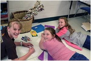 Kenzie O'Dell (left), Olivia Parsons and Chelsea Reed color in their graphic design.