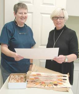 Library Aide Donna Kellison (left) and Library Director Ann Farr review publicity materials for 2016 Salad Luncheon.
