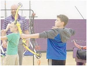 Seventy-five EGMS parents and students recently attended a Percy Jackson themed Math and Literacy Night at the school.  Pictured: Chris Roth, physical education teacher, helping students Isaac Vance and Ayden White with their archery skills.